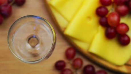 Pouring red wine and cheese snacks on the table