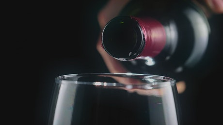 Pouring red wine from a bottle, very close view