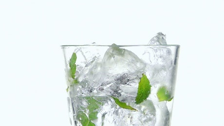 Pouring sparkling water on a glass with mint leaves and ice