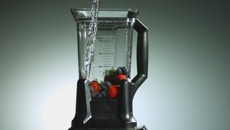 Pouring water into blender with fruit