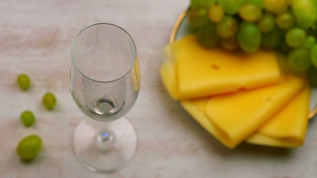 Pouring white wine and a plate of cheese snacks