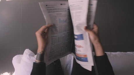 POV flipping through a newspaper