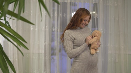 Pregnant woman excited for birth hugs teddy bear and rubs belly