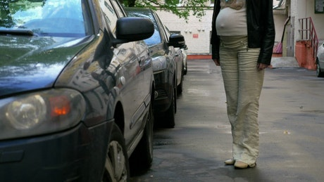 Pregnant woman getting into a car