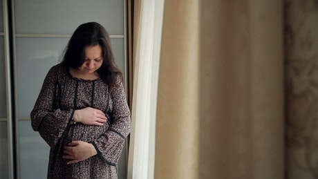 Pregnant woman hugs her tummy with hope