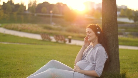 Pregnant woman listening to music in the park