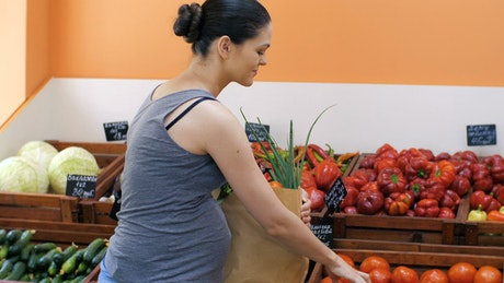 Pregnant woman shopping in a greengrocer