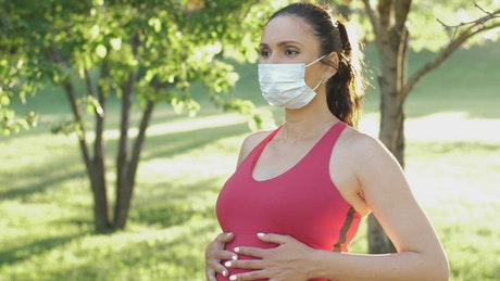 Pregnant woman with mask in the park