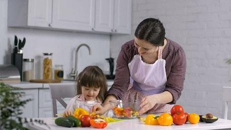 Preparing salad with her daughter
