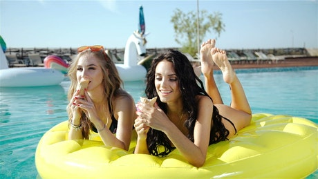 Pretty girls eating ice cream on pool floats