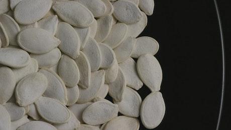 Pumpkin seeds on a black plate