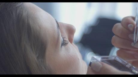 Putting fake lashes on model