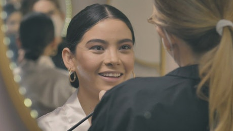 Putting makeup on a bride in front of a mirror