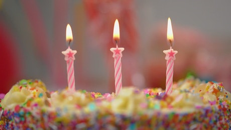 Putting out candles on a colorful cake