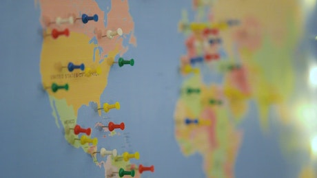 Putting thumbtacks on a world map board