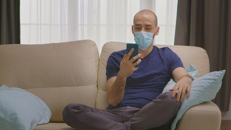 Quarantined man chats on smartphone on couch