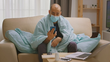 Quarantined man with smartphone video chats on sofa