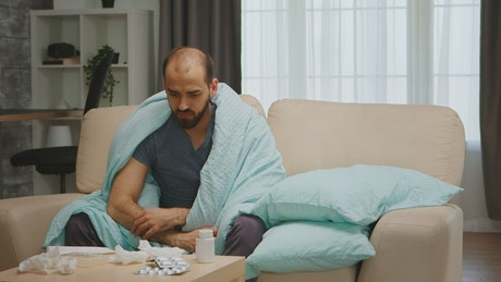 Quarantined sick man sits on sofa holding medication