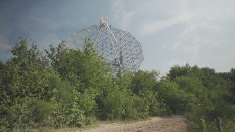Radio telescope behind trees
