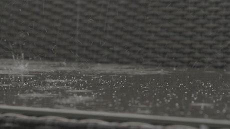 Rain falling onto a bench