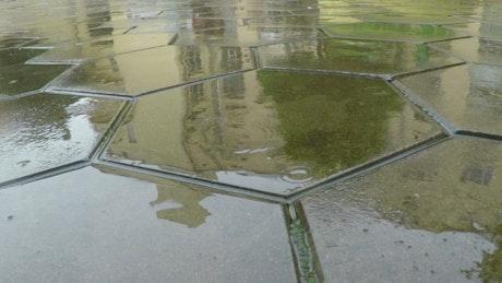 Raindrops falling on the flagstone