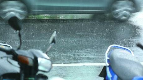 Raining over the city street asphalt