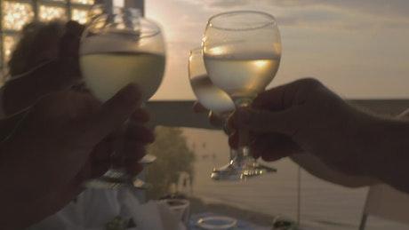 Raising wine glasses at sunset