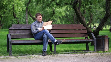 Reading a newspaper in the park