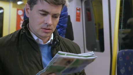 Reading a newspaper on the train