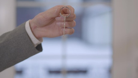 Realtor hand holds key and woman takes it