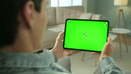 Rear view of green screen tablet swipe in living room