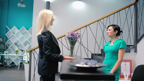 Receptionist listens to a client at the reception