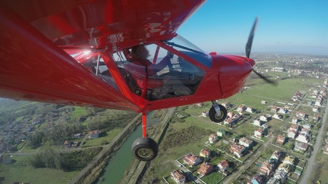 Red aircraft flying above the houses and landing