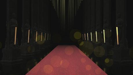 Red carpet between rows of black columns
