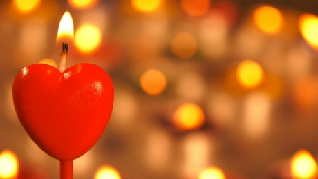 Red heart shaped candle with more candles behind