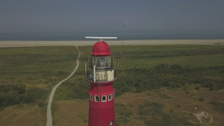 Red lighthouse near the shore, spinning aerial shot