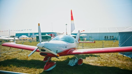 Red plane parked on a display in a field