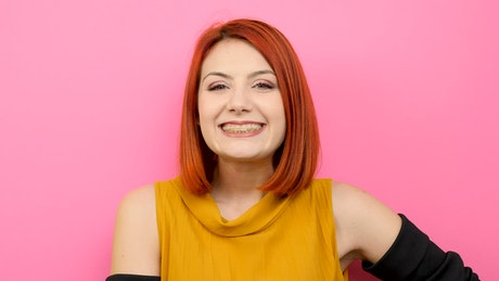 Redhead woman smiling with pink background
