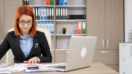 Redhead woman working at her desk