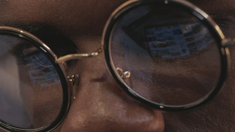 Reflection in the glasses of a man using a tablet