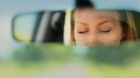 Reflection of a woman in the rear view mirror