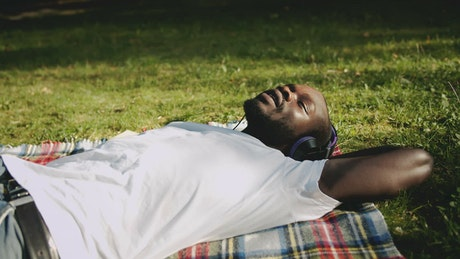 Relaxed man enjoys music while lying on grass