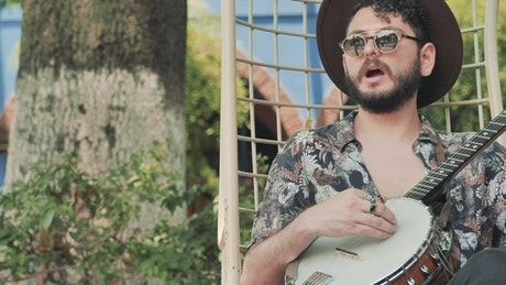Relaxed man with hat and glasses playing the banjo in a garden