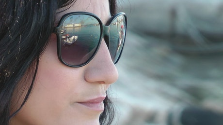 Relaxed woman wearing glasses by the seashore