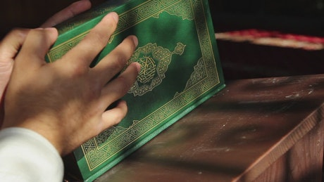 Religious man looking at the pages of the Quran