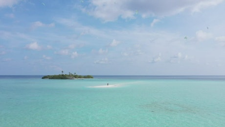Remote tropical island with a couple on a sandbar
