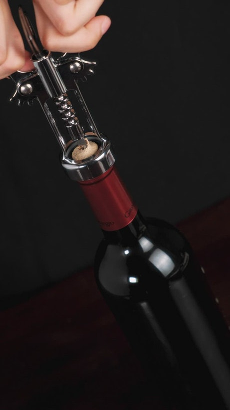Removing the cork from a wine bottle with a corkscrew