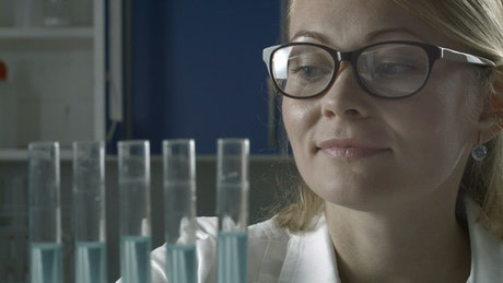 Researcher adding blue liquid to test tubes