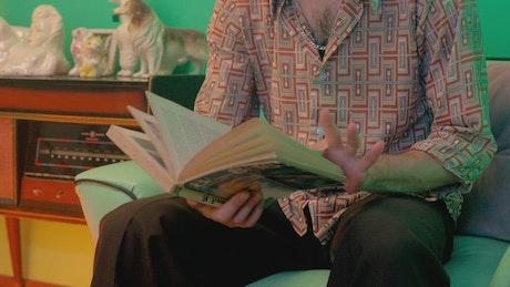 Retro man sitting on sofa reading book
