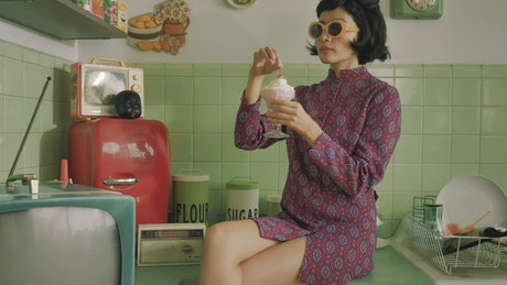 Retro woman eating an ice cream in the kitchen